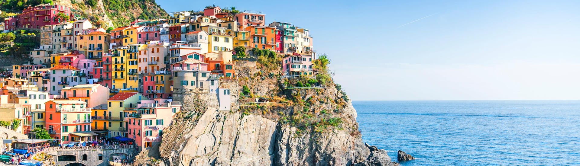 An image of the picturesque little village of Manarola perched on top of the cliffs, one of the sights afforded to those who go on a boat trip along the Cinque Terre coast.