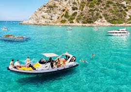 A boat of Sea Sports Tropea stopped in a cove to snorkel in the crystal clear waters of the coast during a boat trip to Capo Vaticano along the Costa degli Dei.