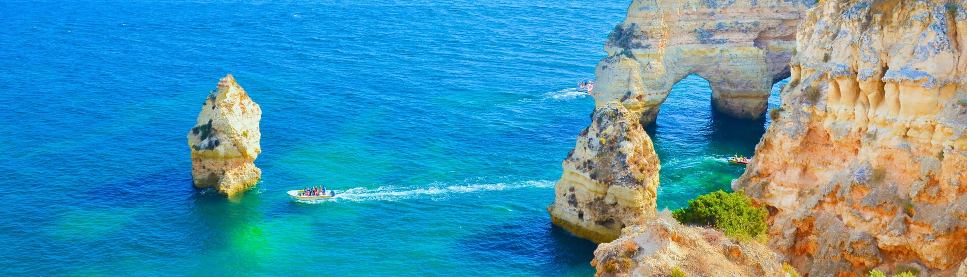 An image of the clear blue waters and the impressive rock formations of the Algarve coastline that visitors can enjoy on a boat trip from Lagos.