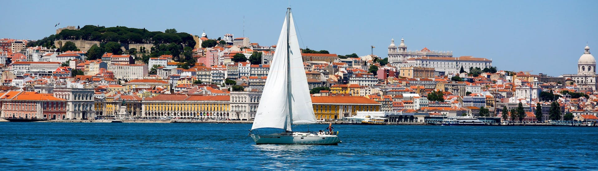 An image of a sailing boat drifting along the Tagus River during a boat trip in Lisbon.