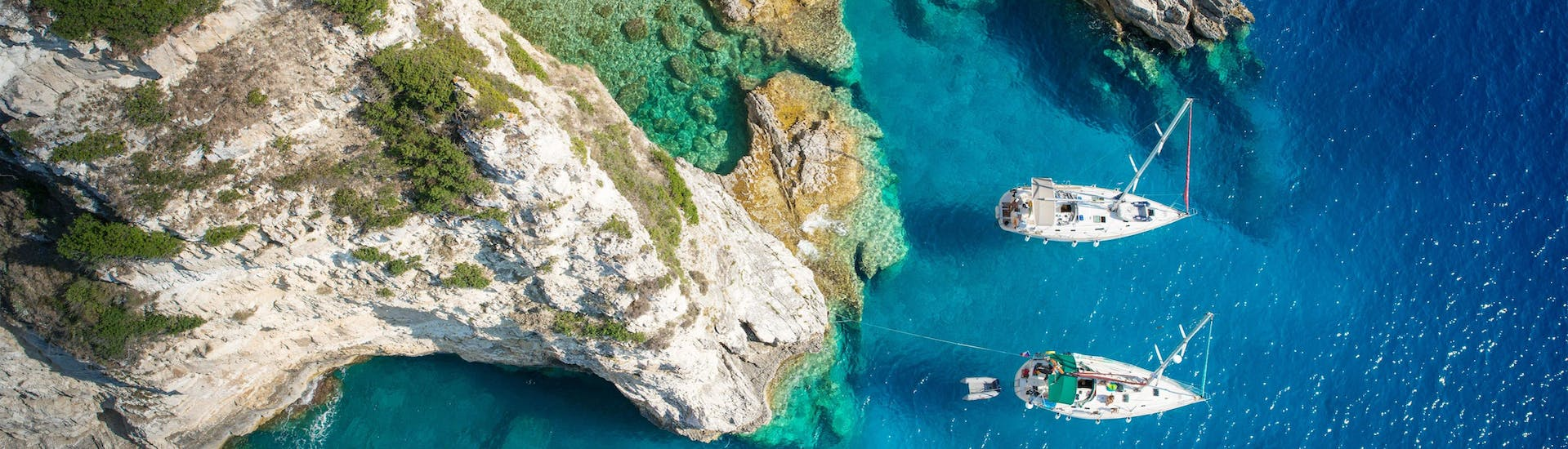 Aerial view of a cove on the island of Paxos where boats are moored, a population destination in Greece for boat trips.