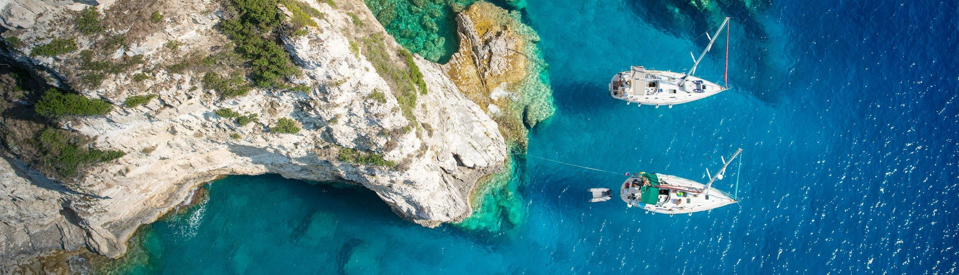 Aerial view of a cove on the island of Paxos where boats are moored, a popular destination in Greece for boat trips.