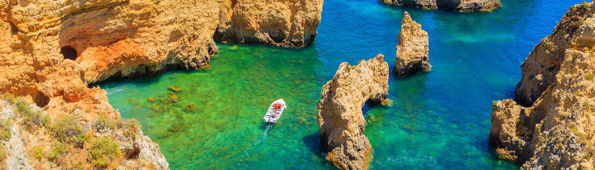 A view of the famous rocks of Ponta da Piedade in Portugal with a number of boat trip operators navigating their boats along the coast.