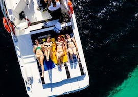 A group of friends laying on the boat and enjoying the sun during the boat trip to Capri with snorkeling with Capitano Ago.