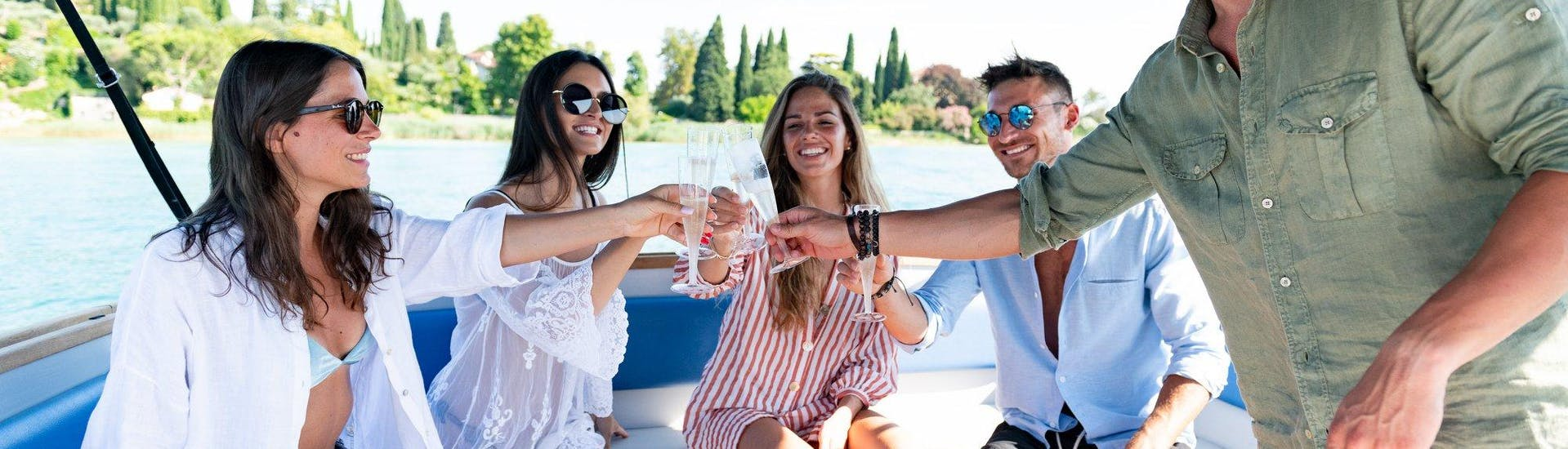 A group of friends raise a glass of wine on board a Sirmione Boats motorboat during a boat trip to the Lake Garda Castles and Bardolino.