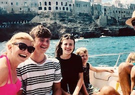 A happy group of people enjoying the boat trip to the Polignano a Mare caves with snorkeling with Dorino Gite in Barca Polignano.