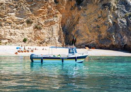 During the Boat Trip to the Wild Beaches of Arrábida Natural Park with Meira Pro Center Sesimbra, the boat is anchored in front of a beach, where the participants can relax and enjoy the clear water.