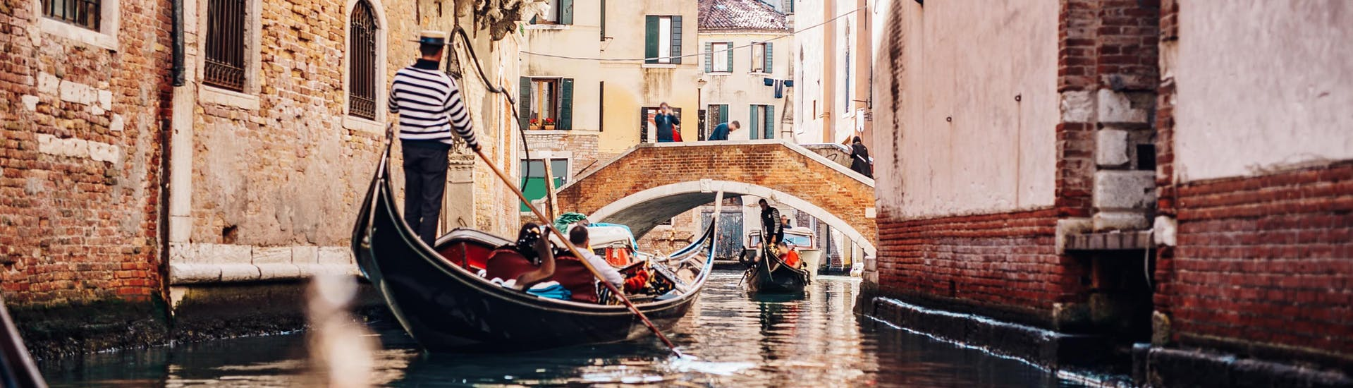 A gondoliere is paddling the boat through a narrow canal on a gondola ride in Venice.