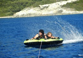 2 people on a towable tube being towed by a motorboat from Gliss1Flo in Saint-Florent.