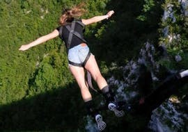 A woman is bungee jumping from the Artuby Bridge, the highest bridge in France for bungee jumping, with Latitude Challenge.