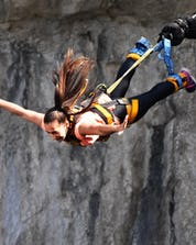 A young woman holds her breath as she falls into the depths while bungee jumping in Valgadena.
