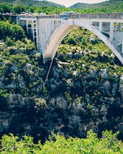 A brave visitor is jumping from Pont de l'Artuby while bungee jumping at Gorges du Verdon.