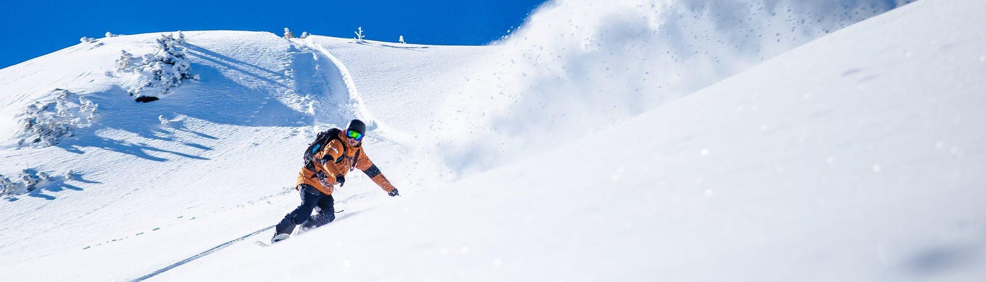 Un snowboardeur glisse sur la poudreuse durant son cours de snowboard avec Cab9 Snowboarding dans le domaine skiable de Val Thorens.