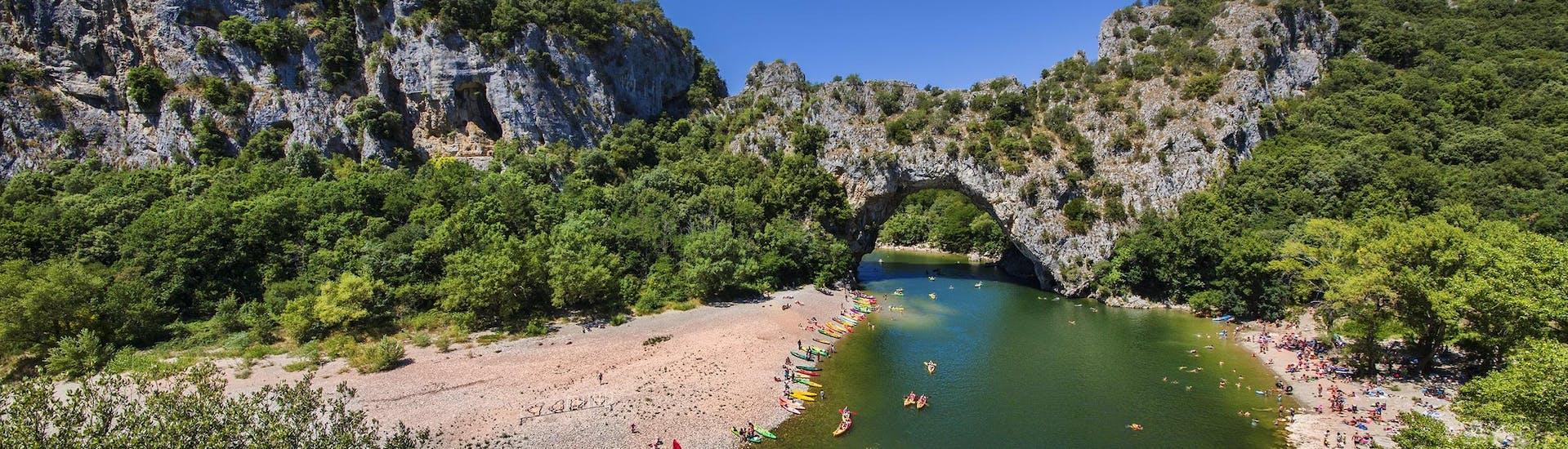 Un groupe de personnes passe sous le Pont-d'Arc en canoë en Ardèche.