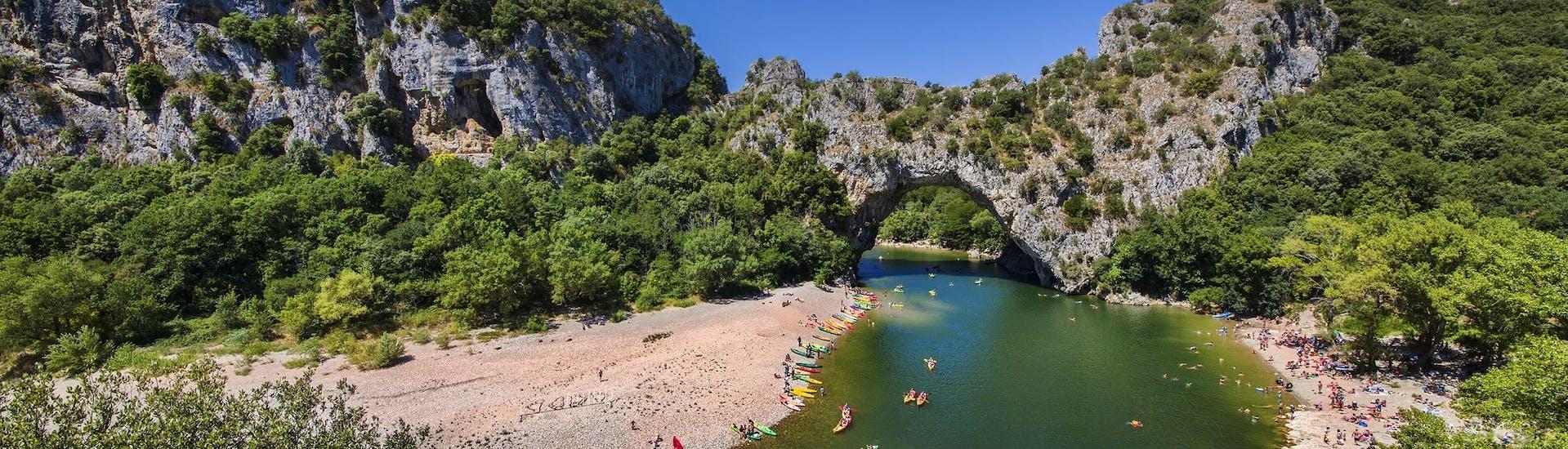 Eine Gruppe an Leuten paddelt beim Kanufahren in Ardèche durch die Pont-D'Arc.