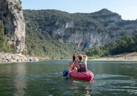 Lors de la descente du tronçon Au cœur de la réserve de 24 km en Ardèche, un couple admire les merveilleux paysages en pagayant dans un canoë loué auprès d'Aigue Vive.