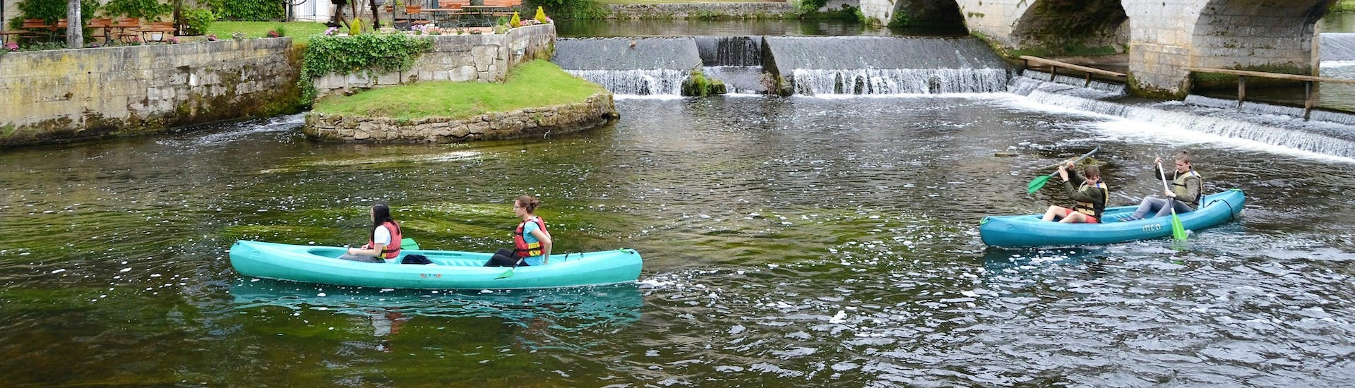 Friends are paddling on the Dronne river in the middle of the charming village of Brantome during their Fontaine d'Amour - 8km canoeing tour with Allo Canoës Dordogne.