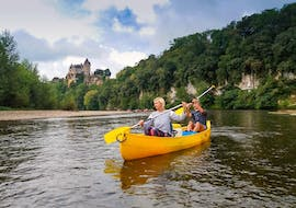 A couple are paddling on the Dordogne River in front of a castle during their 12 km canoe trip with Canoës Loisirs Dordogne.