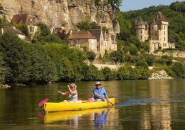 A couple is paddling on the Dordogne River in front of La Roque-Gageac during their 16 km canoe trip with Canoës Loisirs Dordogne.