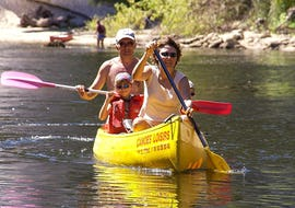 A couple and their child are paddling on the Dordogne River during their 9 km canoe trip with Canoës Loisirs Dordogne.