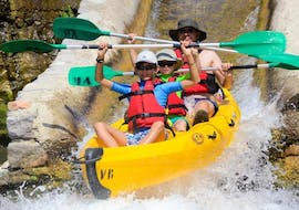 A father and his two kids are paddling down the Ardèche river and are having fun during their Canoe Rental in Ardèche - Maxi-Tour 12km with ALB Canoes.