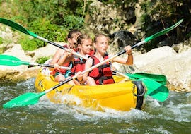 Three kids are paddling down the Ardèche river and are having fun during their Canoe Rental in Ardèche - Mini-Tour 8km with ALB Canoes.