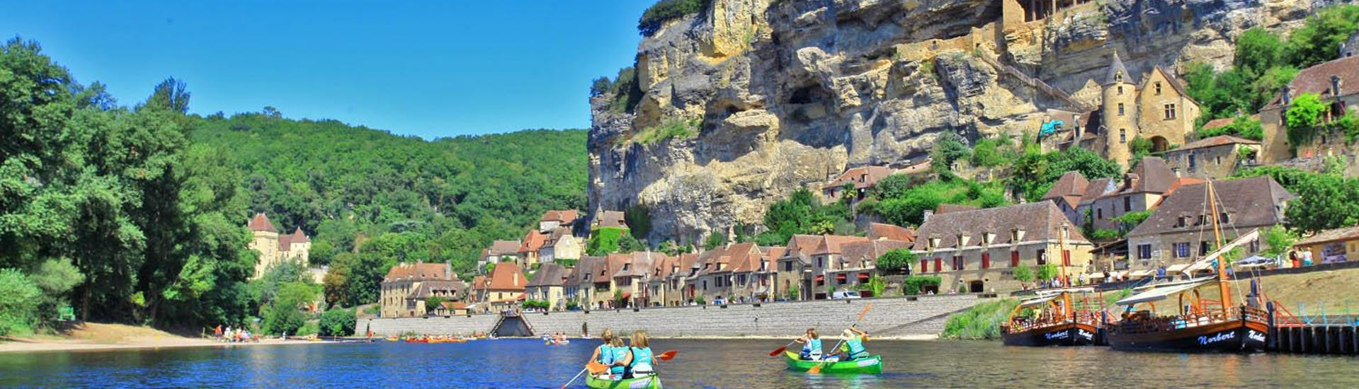 A group of canoes on the Dordogne River is admiring the landscapes during the 25km trip from Carsac with Canoë Dordogne.