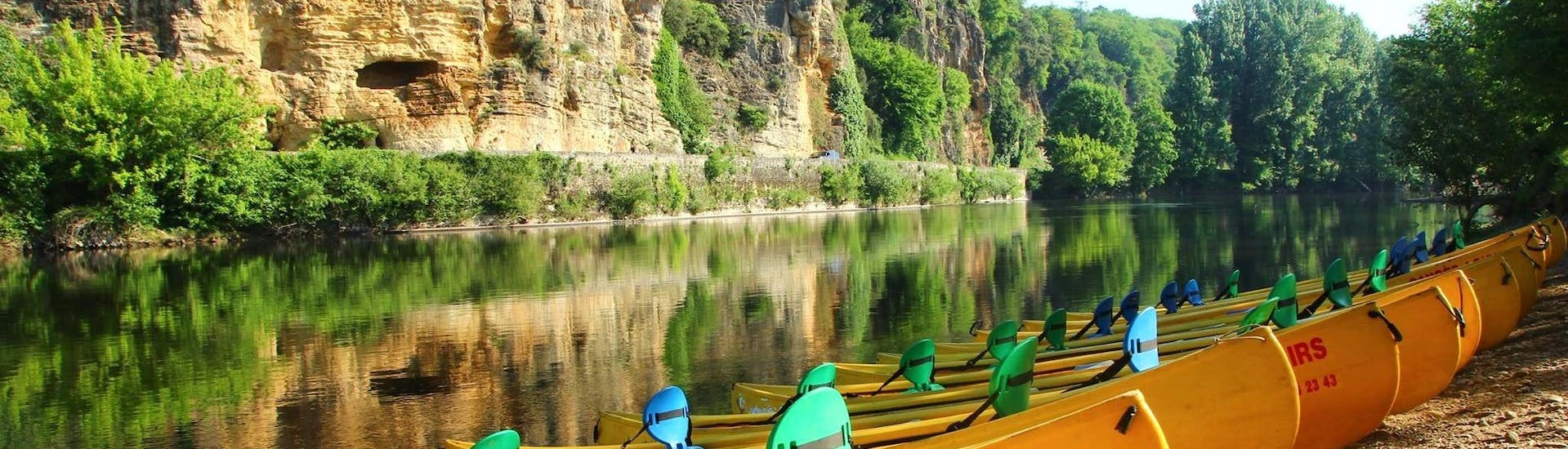 Empty canoes from Canoës Loisirs await holidaymakers on the banks of the Dordogne in the early morning for a canoe trip along the river.