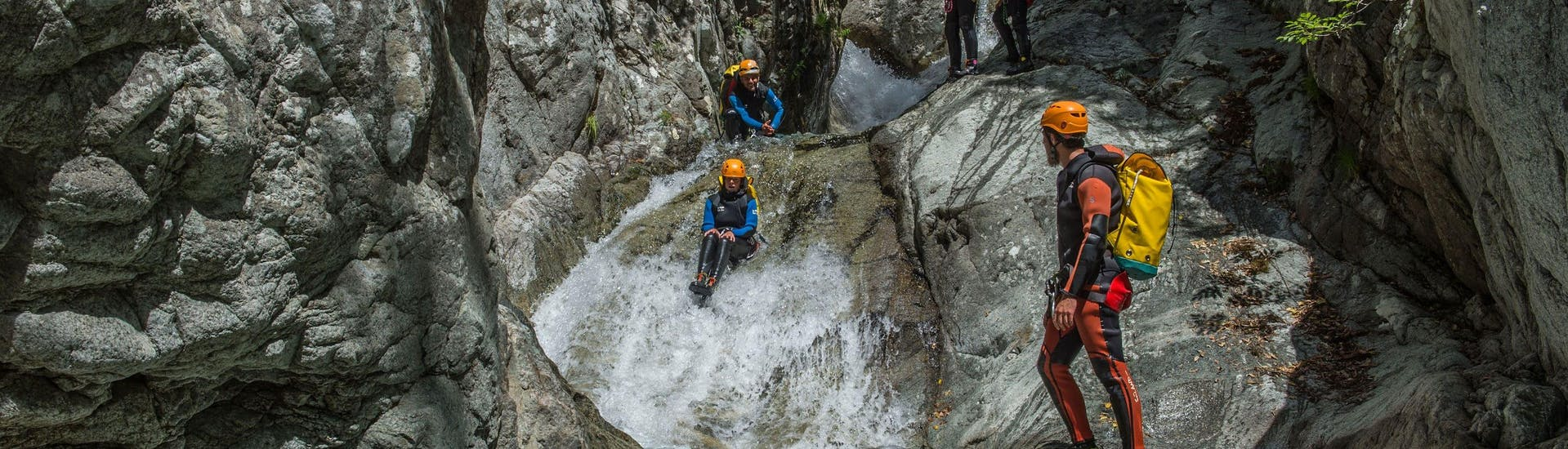 A group slides in the Canyon du Verghellu during the Canyoning Sport activity with their instructor from Canyon Corse.