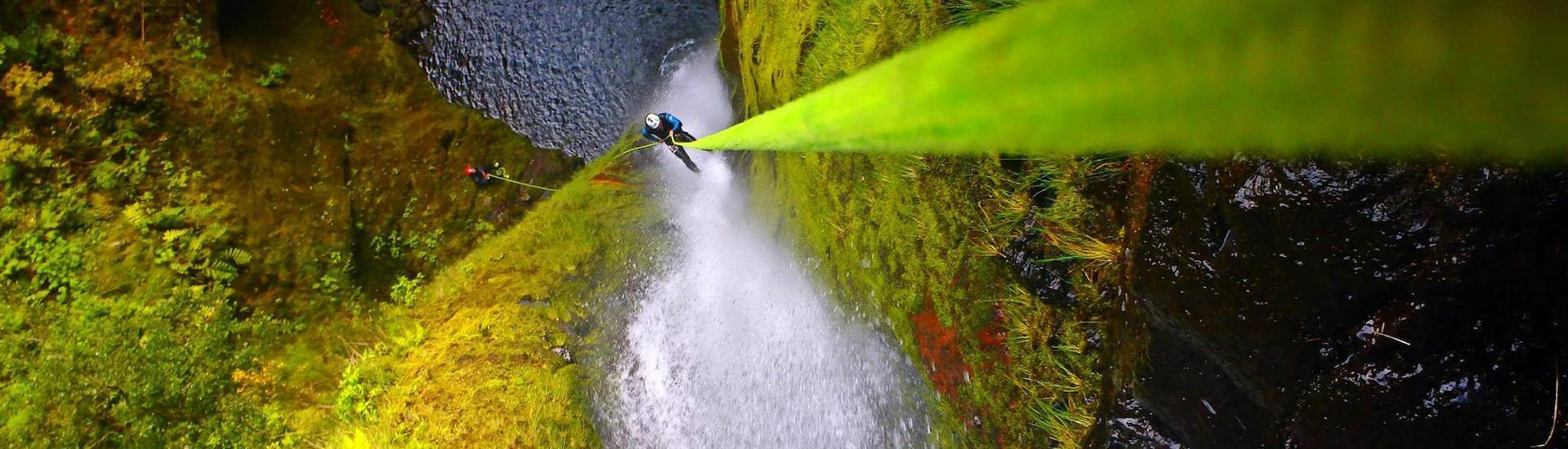 """A participant of the Canyoning """"Advanced"""" in Madeira is abseiling over a high waterfall with the help of an experienced guide from Epic Madeira."""