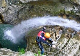 A participant of the Canyoning in Torrente Tignale is slowly abseiling down a rock during the activity organized by LOLgarda.