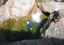 A man is jumping in a natural pool during a Canyoning in Canyon de la Vacca - Aquatic trip with Corsica Madness.