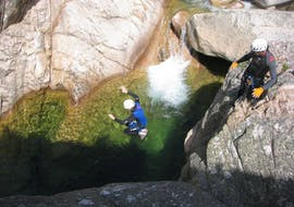 Un homme saute dans une piscine naturelle lors d'une sortie Canyoning dans le canyon de la Vacca - Aquatique avec Corsica Madness.