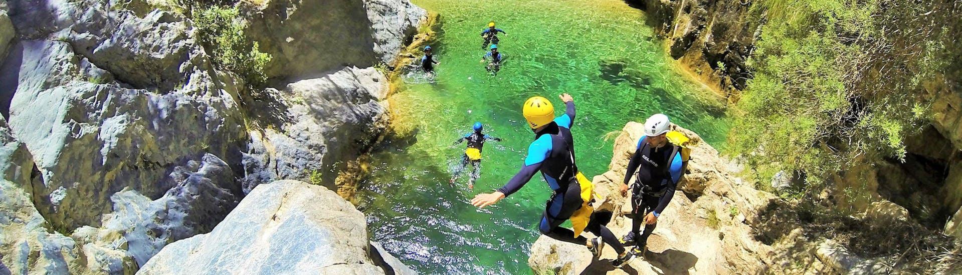 Un grupo de amigos saltan desde el acantilado al agua cristalina durante el Canyoning para Principiantes en Río Verde, organizado por Barranquismo Río Verde.