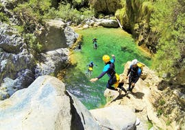 A group of friends jump from the cliff into the crystal clear water during the Canyoning Beginner Tour in Rio Verde, organized by Barranquismo Rio Verde.