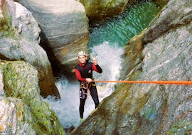 "A participant of the Canyoning ""Blue Lagoon"" in Zemmschlucht is roping down over a high rock cliff with the help of an experienced guide from Freiluftakademie."