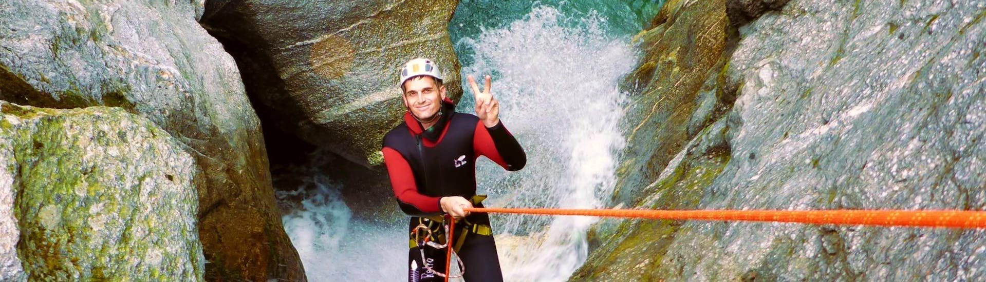 """A participant of the Canyoning """"Blue Lagoon"""" in Zemmschlucht is roping down over a high rock cliff with the help of an experienced guide from Freiluftakademie."""