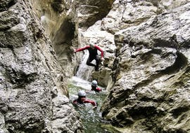 Participants of the canyoning trip Classic in the Nyon Canyon with 7 Aventures are jumping into the water.