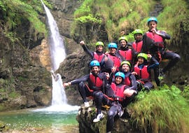 A group of participants of the Canyoning in Rio Nero is posing at the camera on a rock during a canyoning activity organized by LOLgarda.