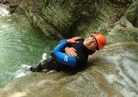 """A man participating in the Canyoning """"Discovery"""" - Canyon d'Angon tour by Térreo Canyoning is sliding down a natural water slide."""