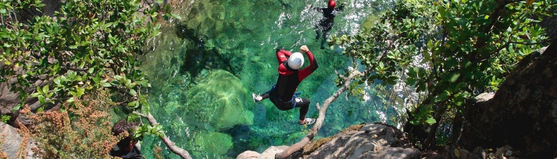 """A participant of Canyoning """"Discovery"""" - Canyon de Pulischellu is jumping into an emerald green natural pool under the supervision of a qualified canyoning guide from Acqua et Natura."""