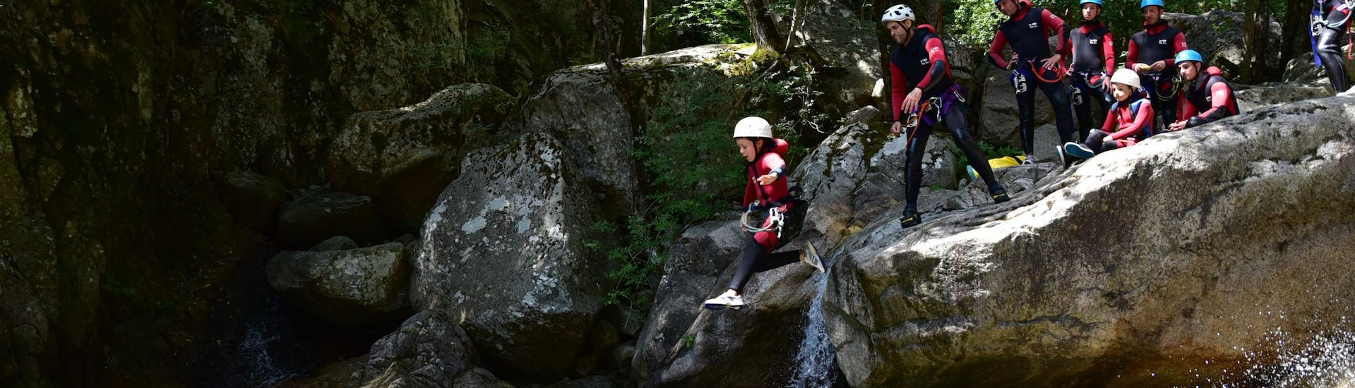 A kid is jumping in a natural pool during a Private Canyoning in Pulischellu - Discovery (12 ppl max) trip with Corsica Madness.