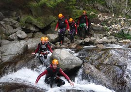 """Canyoning enthusiasts walking on rocks as they progress inside the canyon during their Canyoning """"Discovery"""" - Canyon in Haute Ardèche with Torrents & Granit."""