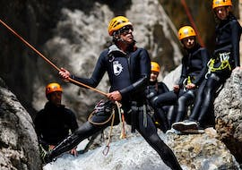 A guide from SerreChe Canyon is showing the participants how to handle an abseiling passage during their Canyoning in Canyon du Fournel - Discovery tour.