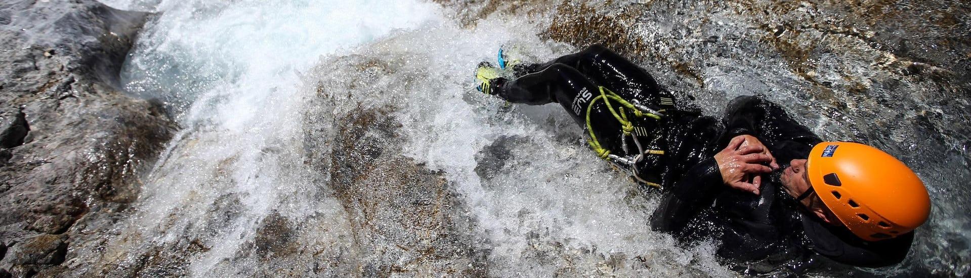 Un homme descend un toboggan naturel lors d'une sortie Canyoning dans le canyon des Acles - Tonique avec SerreChe Canyon.