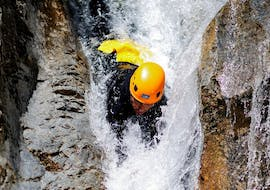 A man is sliding down a natural slide head first during his Canyoning in Canyon des Acles - Dynamic tour with SerreChe Canyon.