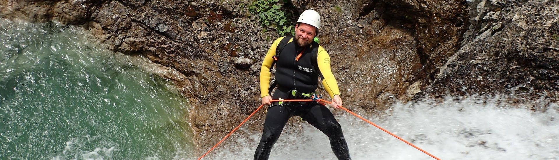 Bei der Extrem Canyoning Tour im Allgäu mit canyoning erleben seilt sich ein Teilnehmer über einen Wasserfall ab.