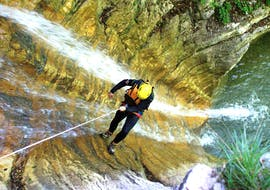 A participant of Extreme Canyoning at Lake Sylvenstein with Montevia is abseiling down a waterfall in the canyon.
