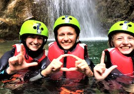 Three participants of the activity Canyoning in Rio Nero - Family are smiling while floating in the water during the activity organized by LOLgarda.