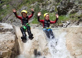"""During the Canyoning """"Family Tour"""" in Rosengartenschlucht, a two children are having fun whilst sliding a natural slide under the supervision of a qualified canyoning guide from WhyNot Adventures."""